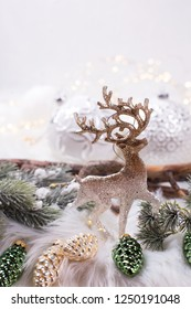 Decorative toy deer, branches fir tree, white balls, green and golden pine cones  on white fur background.