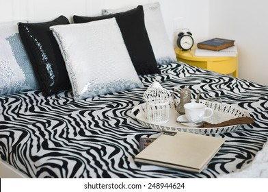 Decorative tray with book,tea set and gloves on the bed