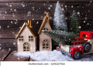 Decorative tree in red car, houses and fur trees    on aged wooden background. Winter holidays decoration. Selective focus.