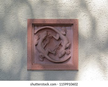 Decorative two lizards embossed detail on a wall with tree shadows