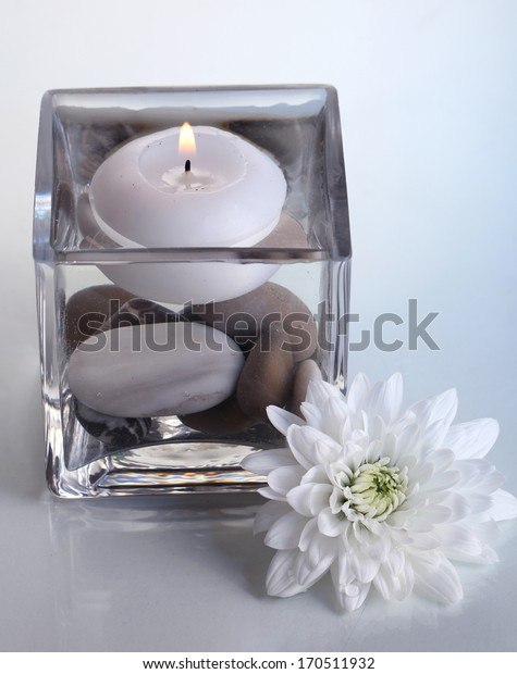 Decorative vase with candle, water and stones on light blue background
