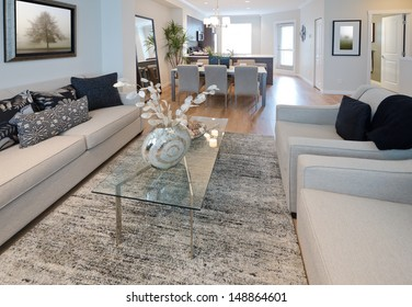 Decorative vase on the coffee table in the living room with the dinner, lunch table at the back. Interior design.