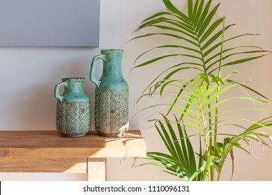 Decorative vases on wooden table with green home plant - cozy stylish home concept
