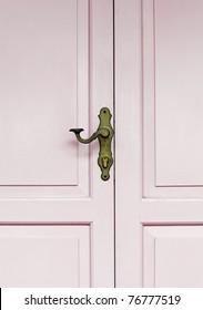A decorative vintage brass door handle on a pink color timber panel door.