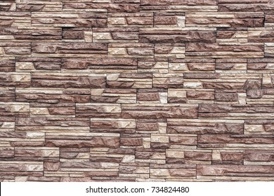 Decorative wall of artificial torn stone in brown tones. Stone masonry in geometric pattern as background or texture.