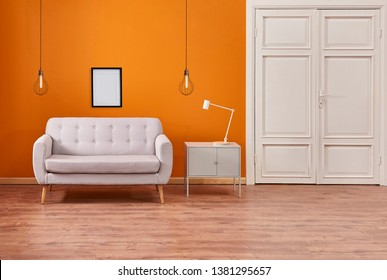 Decorative wall background style orange color and white door with armchair grey cabinet and lamp.