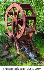 Decorative water wheel in the garden, element of modern landscape design