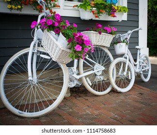 Decorative white bicycles with baskets filled with flowers leaning against a blue wall on a brick sidewalk.