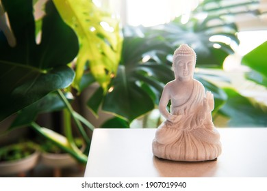 Decorative white Buddha statuette with candles and green monstera plant on the background. Meditation and relaxation ritual. Exotic massage. Selective focus. Copy space