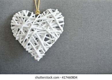 Decorative white heart on grey canvas texture background
