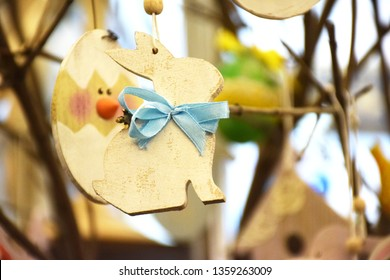 Decorative wooden bunny with blue bow as a decoration for the Easter holiday, copy space.. Decorative wooden rabbit with big heart against the background of a tree branch, selective focus.