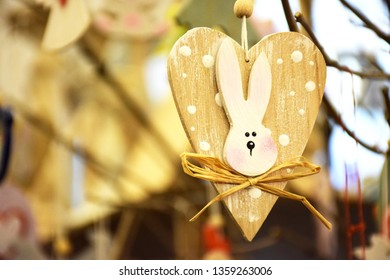 Decorative wooden bunny with heart as a decoration for the Easter holiday, copy space.. Decorative wooden rabbit with big heart against the background of a tree branch, selective focus.