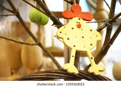 Decorative wooden chicken as a decoration for the Easter holiday. Decorative wooden chicken with a red comb against the background of a tree branch, selective focus.