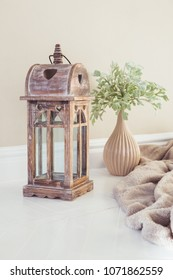 Decorative wooden lantern in retro style. A ceramic vase with a plant, a fluffy soft blanket and a brown lantern on the table.