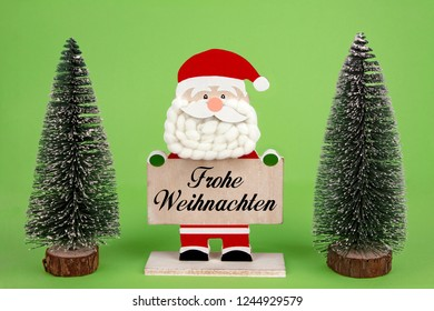 Decorative wooden Santa Clause holding a board with german text -Frohe Weihnachten- means Merry Christmas