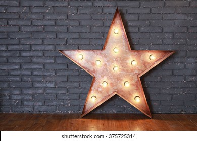 Decorative wooden star with old lamps on a background of gray brick wall. Modern grungy interior