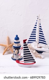 Decorative  wooden toys boats, lighthouse and starfish  on textured  white background. Place for text. Selective focus. Vertical image.