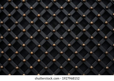 Decorative wrought iron elements of a metal wrought iron gate in dark colors