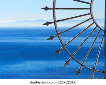 Decorative wrought iron fence by the blue sea Costa Blanca Spain summer vacation background with space for text and graphics