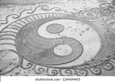 Decorative yin and yang drawing on the sand. Beach vacation leisure concept.  Black and white photo.