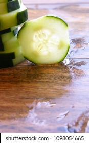 Decoratively sliced cucumber pieces arranged with backlighting to show texture and the interior seed area of the fruit/vegetable.