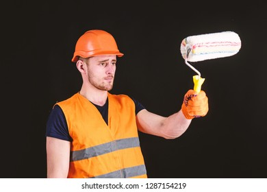 Decorator painting surface in front of himself. Man in helmet, hard hat holds paint roller, black background. Paint and renovate concept. Worker, painter, decorator, contractor, builder on busy face.