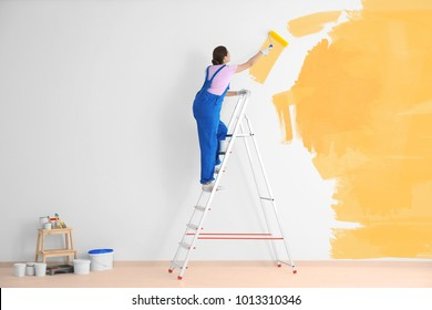 Decorator painting white wall in yellow color with roller