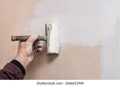 Decorator prime a putty wall before applying a decorative layer of plaster, repairs work in the house, second stage, workflow