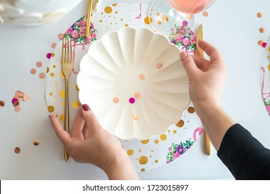 Decorator serving party table in white colors with beautiful white dishes, glasses for wine, golden cutlery. Happy birthday or baby shower for girl. Close up