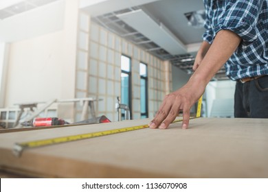 decorator working on design and inspect of plywood at construction site; decorator checking material for interior