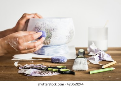 Decoupage hobbyist hands decorating a vase with lavender pattern - some artistic supplies on a table.