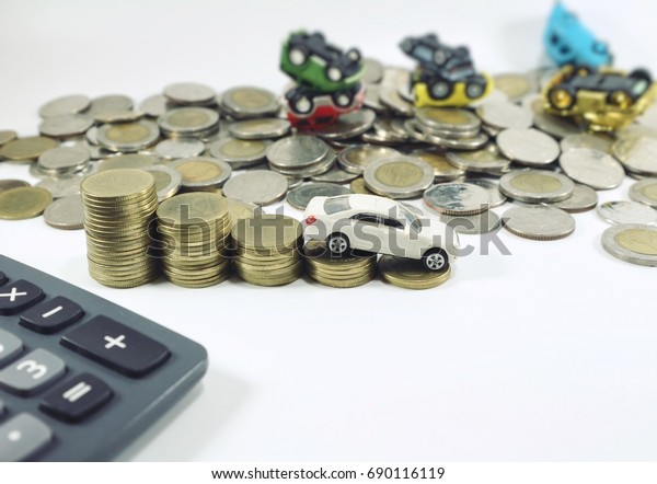 Decreasing profit concept, white car on lowest stair step of rolls coins, car overlapping car on pile money and calculator on white background
