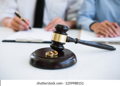 Decree of divorce (dissolution or cancellation) of marriage, husband and wife during divorce process with lawyer or counselor and signing of divorce contract.