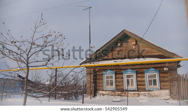 Decrepit old cottage in a snow-covered empty village in Russian, wide angle