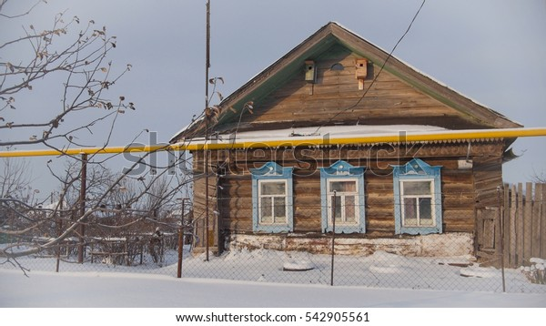 Decrepit old cottage in a snow-covered empty village in Russian, close up, wide angle