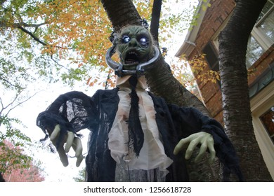 Decrepit Rotting Green Wrinkled Skin Corpse of an Old Ghoul whose Eyes are Glowing Bright Blue as He Hangs in a Suit and Tie with His Head in a Vice from a Tree in Front of Townhomes at Dusk