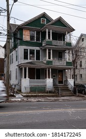 Decrepit unoccupied three-story apartment house with broken and shuttered windows and doors, surrounded by a chain-link fence in the run-down neighborhood.