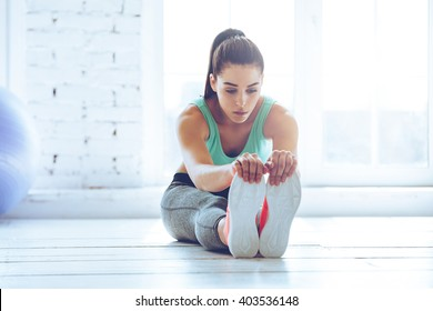 Dedicated to fitness. Front view of beautiful young woman in sportswear doing stretching while sitting on the floor in front of window at gym
