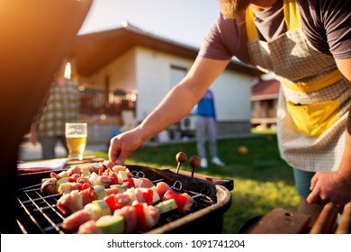 Dedicated man turning vegetables and meat on a stick to grill on other side as well while rest of the family is scattered around the house yard.