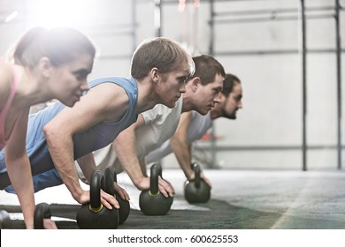Dedicated people doing pushups with kettlebells at  gym