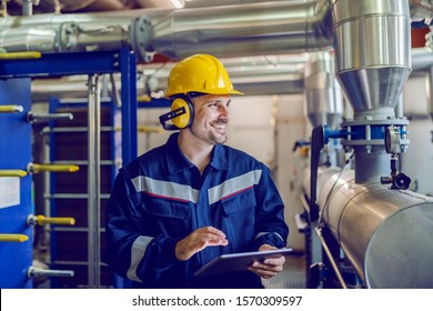 Dedicated smiling factory worker standing next to boiler and holding tablet. Worker is dressed in protective uniform, having hardhat and antiphons.