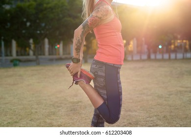 Dedicated woman runner with tattoos warming up stretching her muscles before her workout run jog in the city