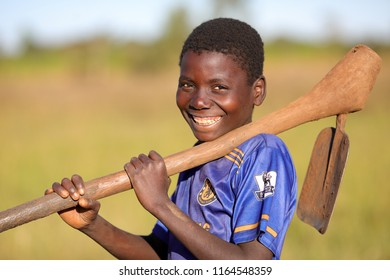 DEDZA, MALAWI - JUNE 3, 2018: Unidentified happy boy in a field with a hoe in a remote village near Dedza. Malawi is one of the poorest countries in the world.