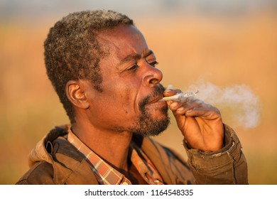 DEDZA, MALAWI - JUNE 5, 2018: Unidentified old farmer smokes a cigarette in the fields near Dedza. Malawi is one of the poorest countries in the world.