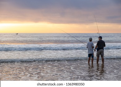 Dee Why, NSW / Australia - March 24th 2019: a father and his son are fishing at sunrise on a famous Sydney beach.