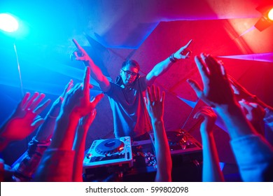 Deejay and crowd raving in disco club