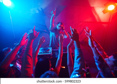 Deejay in headphones raising his hand and enjoying disco with the crowd