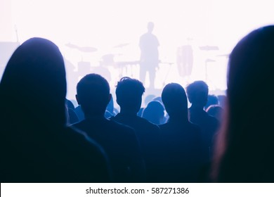 deejay silhouette on a stage with white background and the crowd looking at him