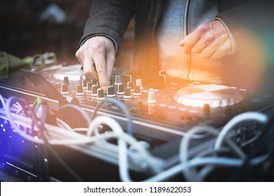 DeeJay using turntable.  Focus on the hands that turn the potentiometers of the mixer