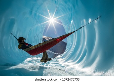 Deep in the Alaskan wilderness, an ice climber rests in a hammock set up in the walls of an ice cave. Sun shines into the entrance of the large blue cavern.